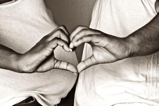black and white photo of a pregnant woman and partner standing belly to belly, making a heart with their hands