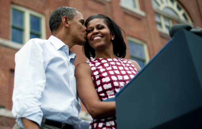 US President Barack Obama (L) kisses First Lady Michelle Obama (R) as they arrive to deliver remarks during a campaign event at the Alliant Energy Amphitheater in Dubuque, Iowa, August 15, 2012, during his three-day campaign bus tour across the state.