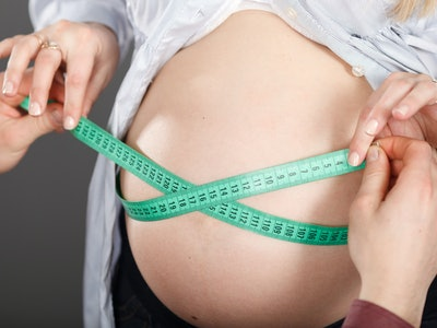 woman measuring pregnant belly with a tape measure