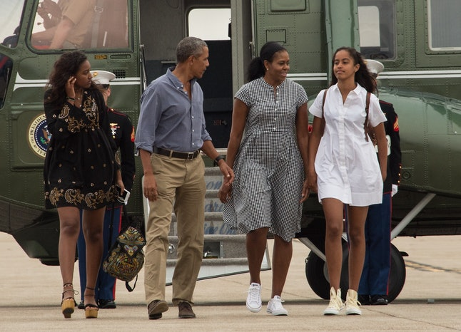 US President Barack Obama, First Lady Michelle Obama and daughters Malia and Sasha walk to board Air Force One at Cape Cod Air Force Station in Massachusetts on August 21, 2016 as they depart for Washington after a two-week holiday at nearby Martha's Vineyard.