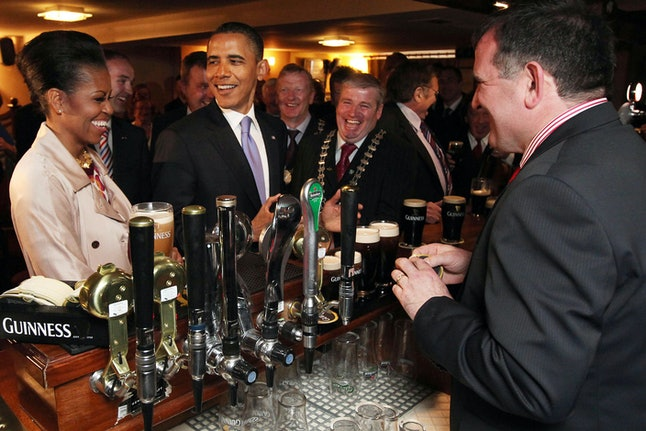 US President Barack Obama (2ndL) and First Lady Michelle Obama (L) laugh prior to tasting a Guinness at a pub as they visit Moneygall village in rural County Offaly, Ireland, where his great-great-great grandfather Falmouth Kearney hailed from, on May 23, 2011. Obama landed in Ireland on May 23, 2011 for a visit celebrating his ancestral roots, kicking off a four-nation European tour.