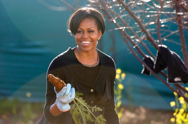 US First Lady Michelle Obama holds up a carrot as she gardens during  a community service project at Vhuthilo Community Center in Soweto township, Johannesburg, South Africa, June 22, 2011.