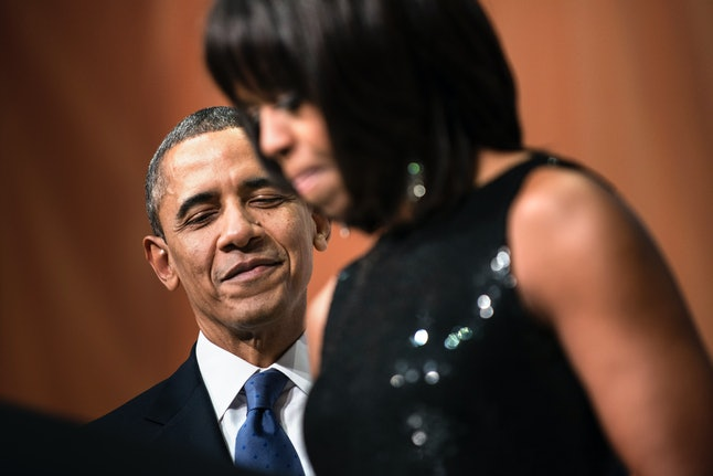 US President Barack Obama listens while US first lady Michelle Obama speak during an inauguration reception at the National Building Museum January 20, 2013 in Washington, DC. US President Barack Obama and US Vice President Joseph R. Biden, who were officially worn in for their second term earlier today, will participate in a ceremonial inauguration on Monday.