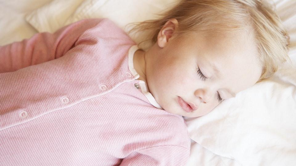 1-year-old sleeping in her crib