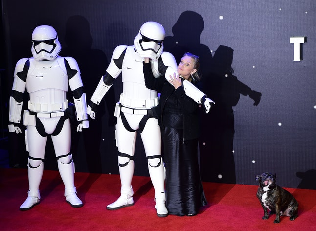 US actress Carrie Fisher (R) poses with a storm trooper as she attends the opening of the European Premiere of 'Star Wars: The Force Awakens' in central London on December 16, 2015. Ever since 1977, when 'Star Wars' introduced the world to The Force, Jedi knights, Darth Vader, Wookiees and clever droids R2-D2 and C3PO, the sci-fi saga has built a devoted global fan base that spans the generations.