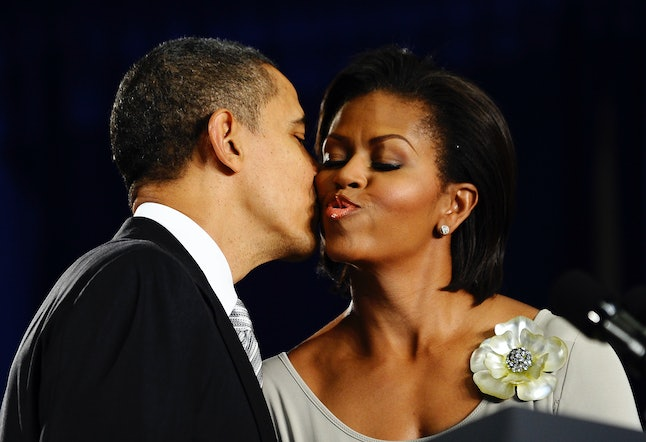 US President Barack Obama kisses First Lady Michelle Obama before signing into law the Healthy, Hunger-Free Kids Act of 2010 at Harriet Tubman Elementary School in Washington on December 13, 2010.
