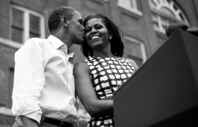 BLACK AND WHITE VERSION - US President Barack Obama (L) kisses First Lady Michelle Obama (R) as they arrive to deliver remarks during a campaign event at the Alliant Energy Amphitheater in Dubuque, Iowa, August 15, 2012, during his three-day campaign bus tour across the state.