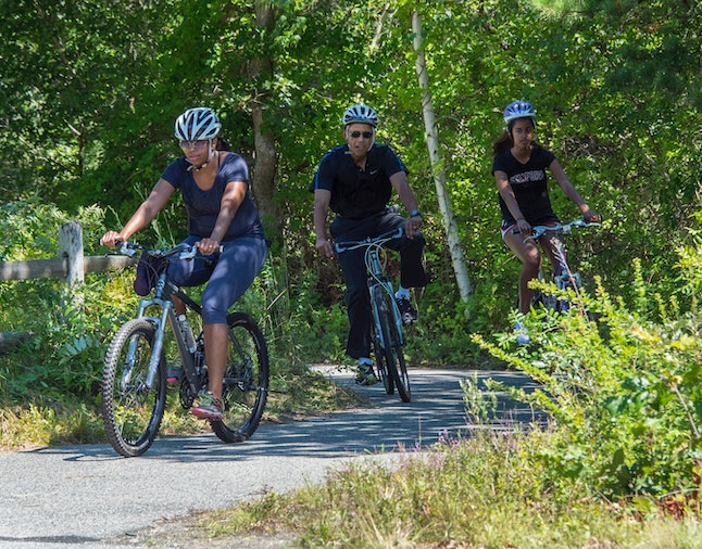 WEST TISBURY, MA - AUGUST 15:  U.S. President Barack Obama(C), First Lady Michelle Obama and daughter Malia Obama ride bikes along the Correllus State Bike Path on August 15, 2014 outside of West Tisbury, Martha's Vineyard, Massachusetts.  The President and his family are currently on vacation in Martha's Vineyard. (Photo by Rick Friedman-Pool/Getty Images)