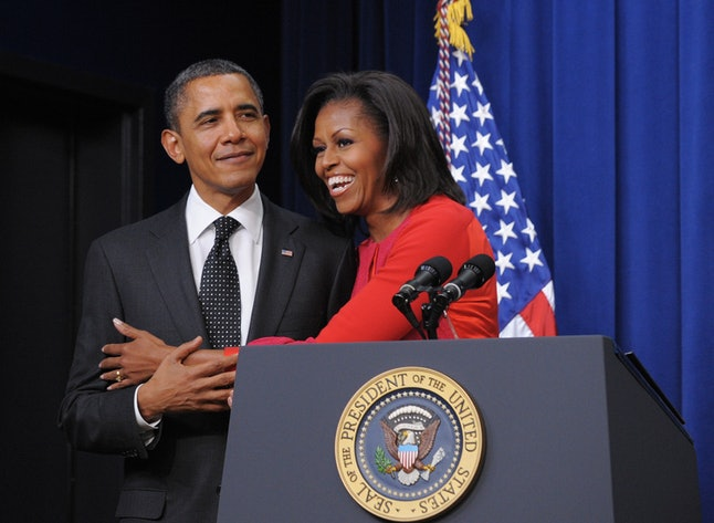 First Lady Michelle Obama embraces US President Barack Obama during a signing ceremony for a bill which provides tax credits to companies to put veterans back to work November 21, 2011 in the South Court Auditorium, next to the White House in Washington, DC.