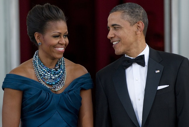 US President Barack Obama and First Lady Michelle Obama await the arrival of British Prime Minister David Cameron and his wife, Samantha Cameron, prior to a State Dinner as part of an official visit on the North Portico of the White House in Washington, DC, March 14, 2012.