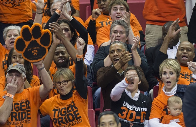 US President Barack Obama, alongside his brother-in-law Craig Robinson (R), attends a NCAA Division I Women's College Basketball tournament game between Princeton and Green Bay at the XFINITY Center in College Park, Maryland, March 21, 2015. Princeton forward Leslie Robinson is Obama's niece.