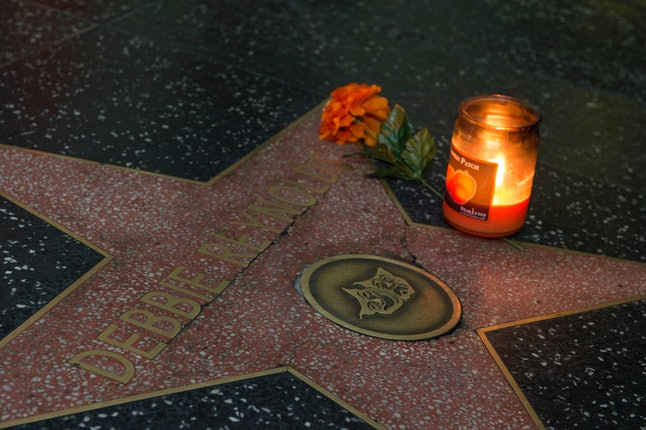A candle is seen on the star for Debbie Reynolds on the Hollywood Walk of Fame in Hollywood, California, on December 28, 2016, after the death of the actress. Debbie Reynolds, the 'Singin' in the Rain' actress who tap-danced her way into American hearts as a star of Hollywood's Golden Age, died, grief-stricken over daughter Carrie Fisher's death a day earlier.