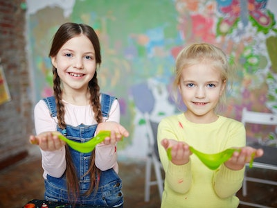 two little girls holding green slime
