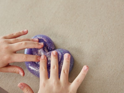 A picture of a child playing with sparkly Elmer's Glue slime.