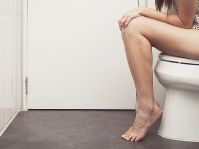 side view of woman in a thigh down shot on the toilet with hands on knees