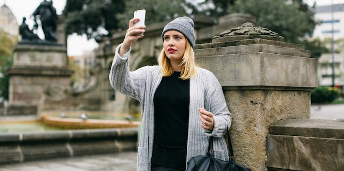 A woman standing alone looks at her phone.