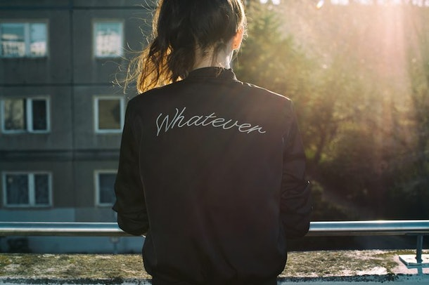 """Woman facing away, wearing a jacket that says """"whatever"""" on the back"""