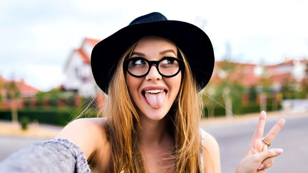 A woman in a black floppy hat, glasses, and a sweater sticks out her tongue and makes a peace sign while taking a selfie.