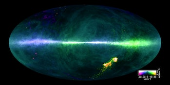 The image colors reflect gas at differing velocities. The plane of the Milky Way runs horizontally across the middle of the image. The Magellanic Clouds can be seen at the lower right.
