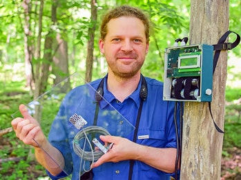 Prof. Dan Mennill with a flight call microphone and a digital recorder for recording migratory birds.