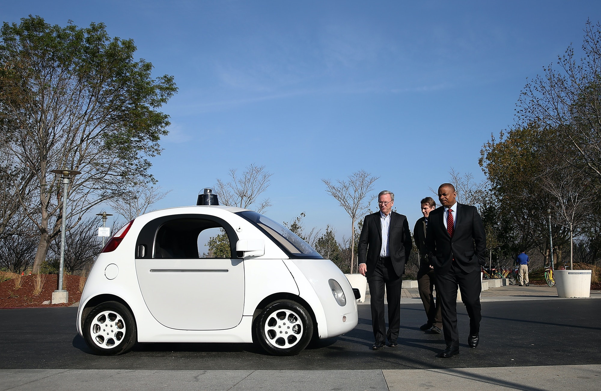 MOUNTAIN VIEW, CA - FEBRUARY 02: U.S. Transportation Secretary Anthony Foxx (R) and Google Chairman Eric Schmidt (L) walk around a Google self-driving car at the Google headquarters on February 2,2015in Mountain View, California. U.S. Transportation Secretary Anthony Foxx joined Google Chairman Eric Schmidt for a fireside chat where he unveiled Beyond Traffic, a new analysis from the U.S. Department of Transportation that anticipates the trends and choices facing our transportation system over the next three decades. (Photo by Justin Sullivan/Getty Images)