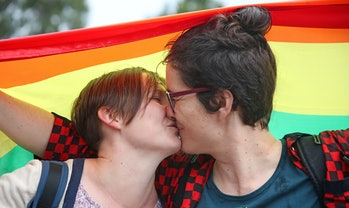 Alice Bennett and her partner Miranda Hill kiss as they gather with a crowd of people to watch a lar...