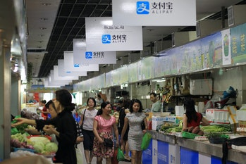 WENZHOU, CHINA - SEPTEMBER 14: (CHINA OUT) Consumers purchase at a local market with boards of Alipay hung up on September 14,2015in Wenzhou, Zhejiang Province of China. Over 70 stalls in a local market started to use Alipay, a popular online payment service in China, to receive money from consumers. Consumers scan the QR to pay for their purchase in the WiFi covered market in Wenzhou. (Photo by VCG/VCG via Getty Images)