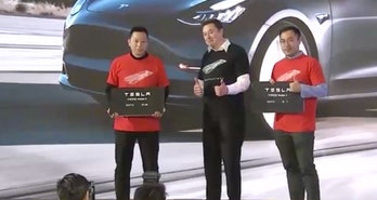 Musk hands over two giant key cards.