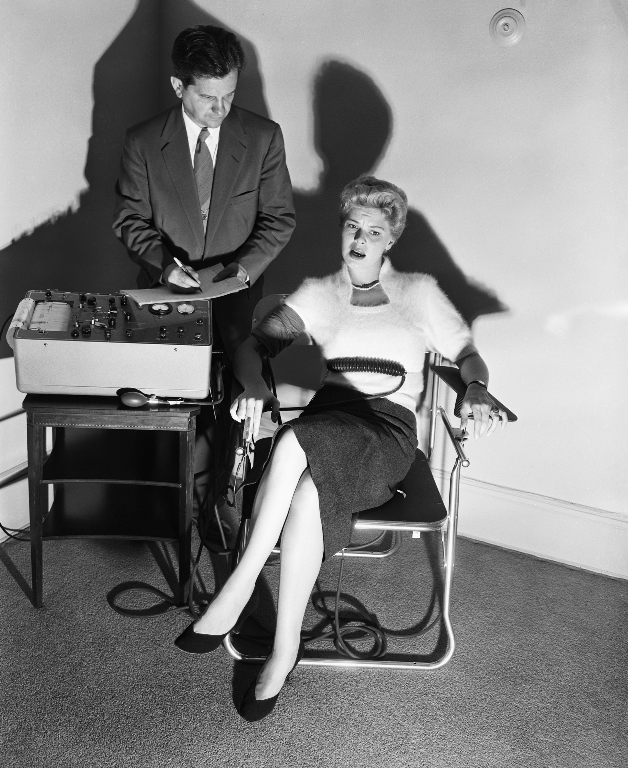 Original Caption: 6/4/1954- Lie detector being demonstrated by Dr. Fred Inbau, professor of criminal law at Northwestern University. Photo shows Dr. Inbau giving the test to pretty Betsey Palmer.