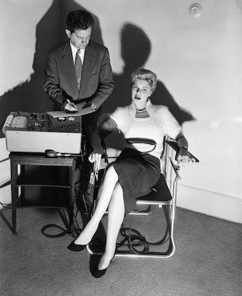 Original Caption: 6/4/1954- Lie detector being demonstrated by Dr. Fred Inbau, professor of criminal law at Northwestern University. Photo shows Dr. Inbau giving the test to pretty Betsey Palmer.