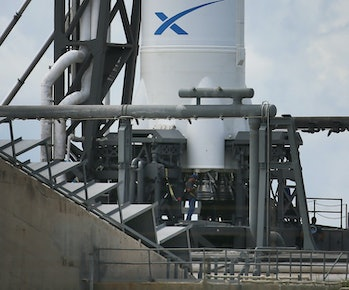 CAPE CANAVERAL, FL - OCTOBER 07: A worker is seen near the engines for the SpaceX Falcon 9 rocket attached to the cargo-only capsule called Dragon as it sits on the launch pad for a scheduled evening launch on October 7,2012in Cape Canaveral, Florida. The rocket will bring cargo to the International Space Station that consists of clothing, equipment and science experiments. (Photo by Joe Raedle/Getty Images)