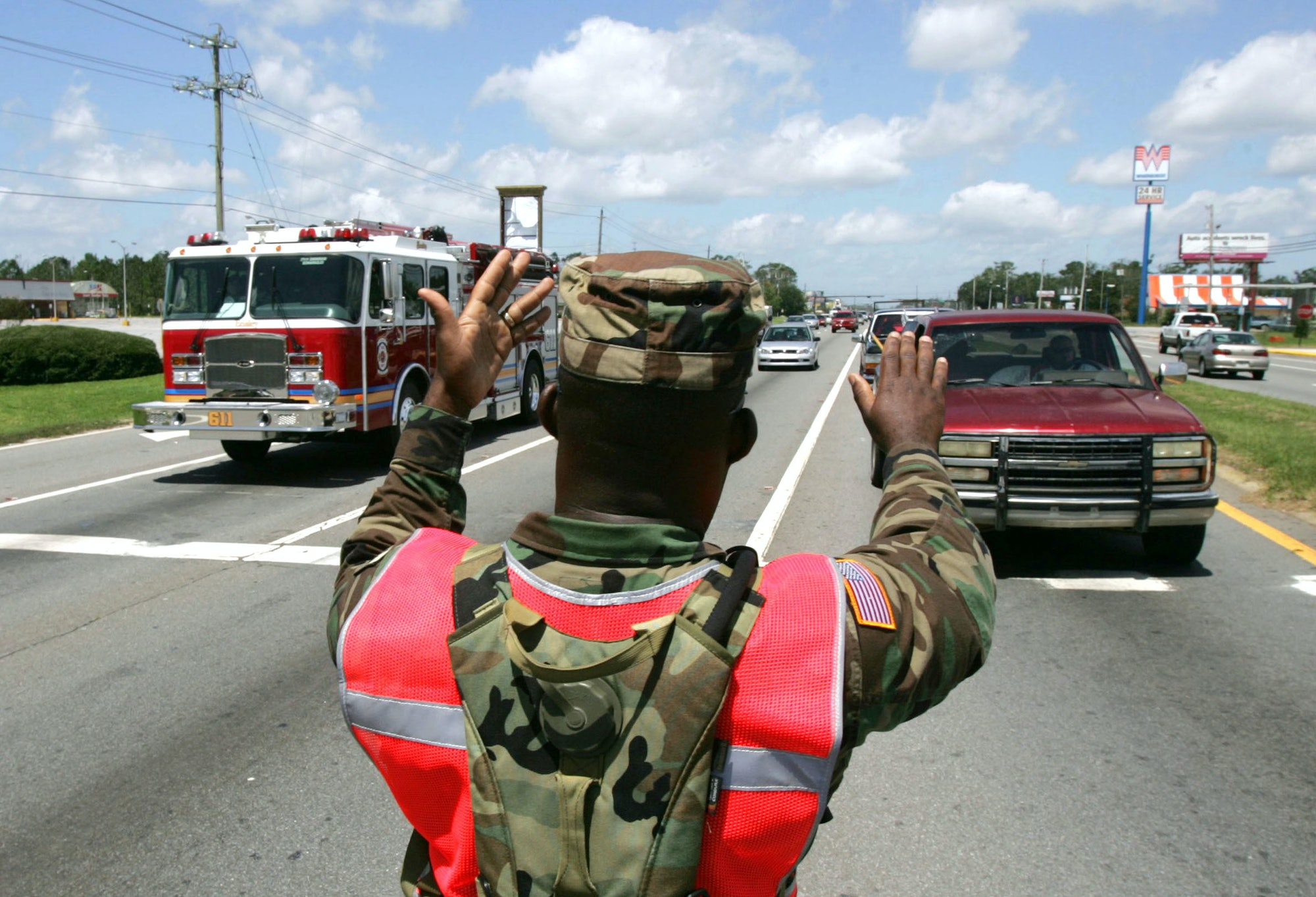 PENSACOLA, FL - JULY 11: US National Guardsman Sgt. Robert Gaines directs traffic July 11,2005in inPensacola, Florida. He and other members of the 1st Battalion 265th ADA National Guard unit were activated to help with the recovery efforts from Hurricane Dennis. Traffic became congested as emergency vehicles and returning residents congested the cities roadways. (Photo by John Moore/Getty Images)