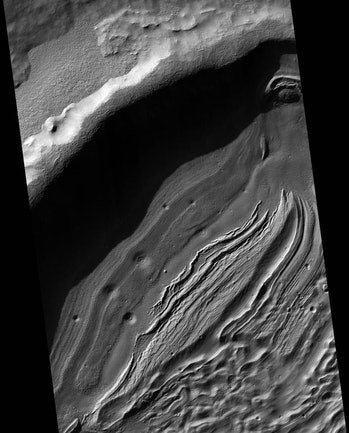With a diameter of about 1,400 miles and a depth reaching the lowest elevations on Mars, Hellas is one of the largest impact craters in the solar system.