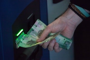 VANCOUVER, BC - OCTOBER 29: A user inserts Canadian currency into the world's first bitcoin ATM in e...