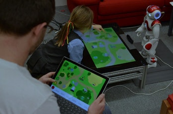 Child interacting with the robotic teaching aid during a laboratory test before heading to the primary schools