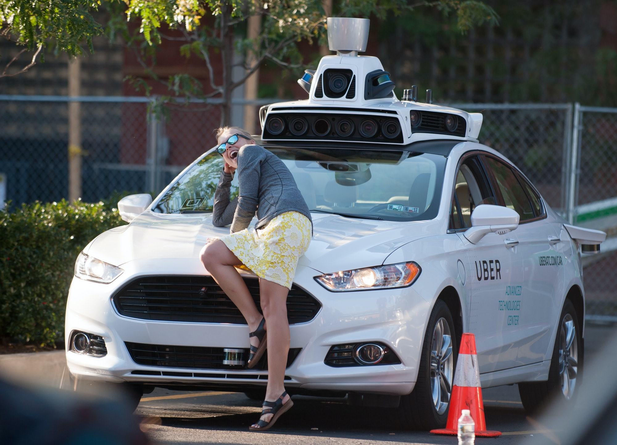 PITTSBURGH, PA - SEPTEMBER 22: A woman poses with an Uber driverless Ford Fusion as it sits in the Uber Technical Center parking lot onSeptember,22, 2016 in Pittsburgh, Pennsylvania. Uber has built its Uber Technical Center in Pittsburgh and is developing an autonomous vehicle that it hopes will be able to transport its millions of clients without the need for a driver. (Photo by Jeff Swensen/Getty Images)