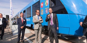 German politicians stand in front of a hydrogen-powered train developed by Alstom.