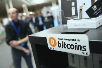 HANOVER, GERMANY - MARCH 16: A sign in French that reads: 'We accept bitcoins' hangs at a display of the LedgerWallet Nano USB stick that enables security-protected transactions with bitcoins at the 2015 CeBIT technology trade fair on March 16, 2015 in Hanover, Germany. China is this year's CeBIT partner. CeBIT is the world's largest tech fair and will be open from March 16 through March 20. (Photo by Sean Gallup/Getty Images)