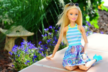 Barbie sitting in garden.