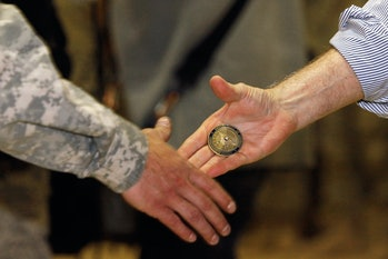 U.S. Defense Secretary Robert Gates presents a 'challenge coin' while shaking hands and posing for photographs with soldiers from the 4th Advise and Assist Brigade, 1stCalvalryDivision out of Fort Hood, Texas while visiting Camp Marez in Mosul, Iraq.
