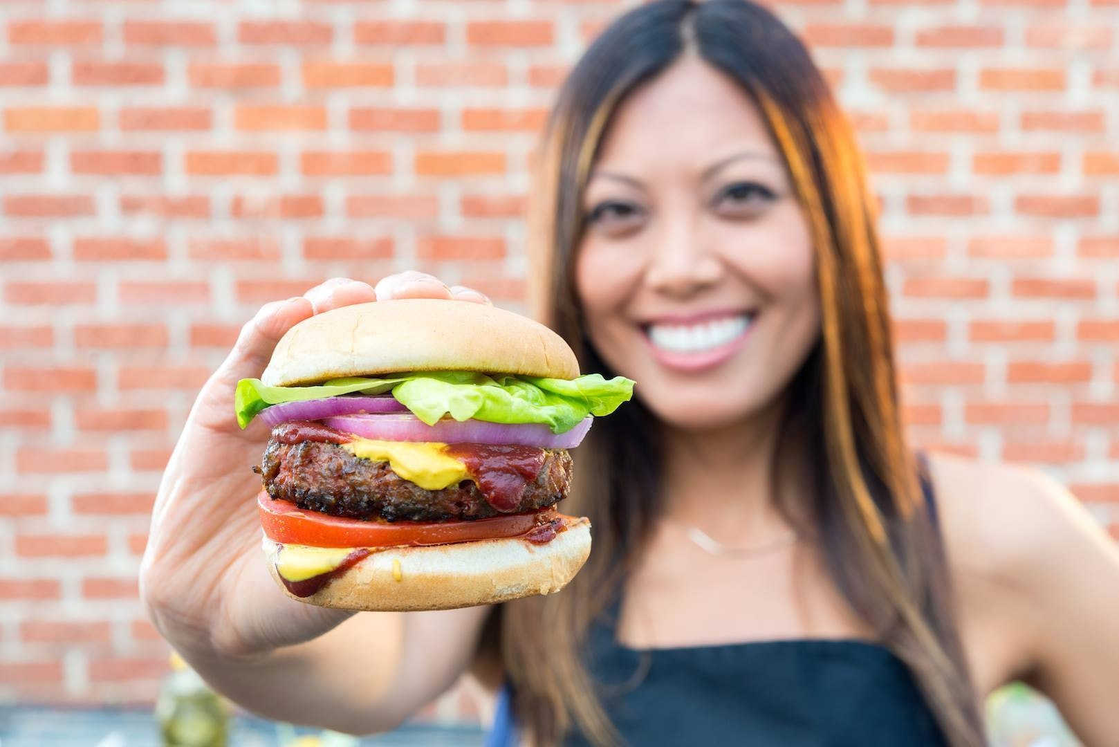 A woman holds the Beyond Burger, a patty made from plant proteins by meat alternative producer Beyond Meat.