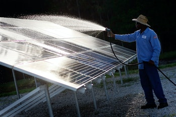 Kindrell Hutchinson washes off a solar panel system at the Leveda Brown Environmental Park and Trans...