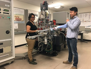 Bose (left) and Jin (right) load asteroid samples into a secondary ion mass spectrometer.