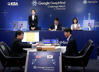 South Korean professional Go player Lee Sedol watches as Google DeepMind's lead programmer Aja Huang puts the Google's artificial intelligence program, AlphaGo's first stone, during the last Google DeepMind Challenge Match on March 12, 2016 in Seoul, South Korea.
