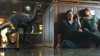 Owen and Claire play a silly game by sliding around a platform to hide from the Indoraptor.