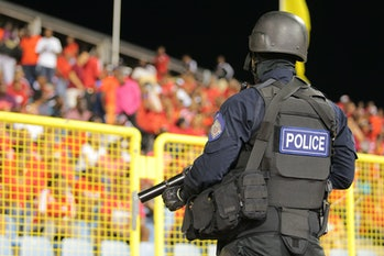 PORT OF SPAIN, TRINIDAD & TOBAGO - NOVEMBER 17: A policeman in full riot gear keeps a close eye during a World Cup Qualifier between Trinidad and Tobago and USA as part of the FIFA World Cup Qualifiers for Russia 2018 at Hasely Crawford Stadium on November 17, 2015 in Port of Spain, Trinidad & Tobago. (Photo by Ashley Allen Getty Images)