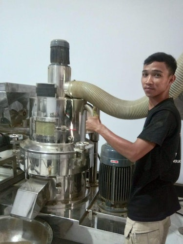 Rio Rinaldi, a kratom seller in Pontianak, Indonesia, with the kratom leaf grinder in his warehouse.