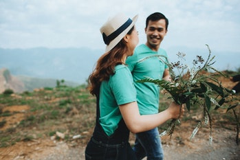 man woman couple smile hike wildflower