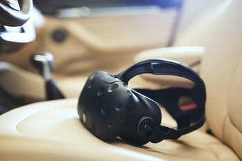 The HTC Vive headset resting on a car seat.