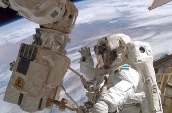 IN SPACE - DECEMBER 14: MissionspecialistChrister Fuglesang waves to the camera as he participates in the second of three planned space walks during construction on the International Space Station on Day 6 December 14,2006in orbit around the Earth. Mission specialist Robert L. Curbeam, Jr. also participated. (Photo by NASA via Getty Images)